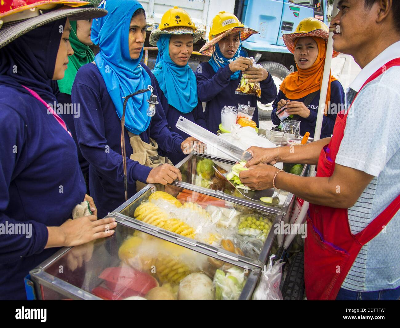 Aug. 18, 2013 - Bangkok, Thailand - Migrant construction workers from Myanmar (Burma) buy fruit from a Thai fruit Stock Photo