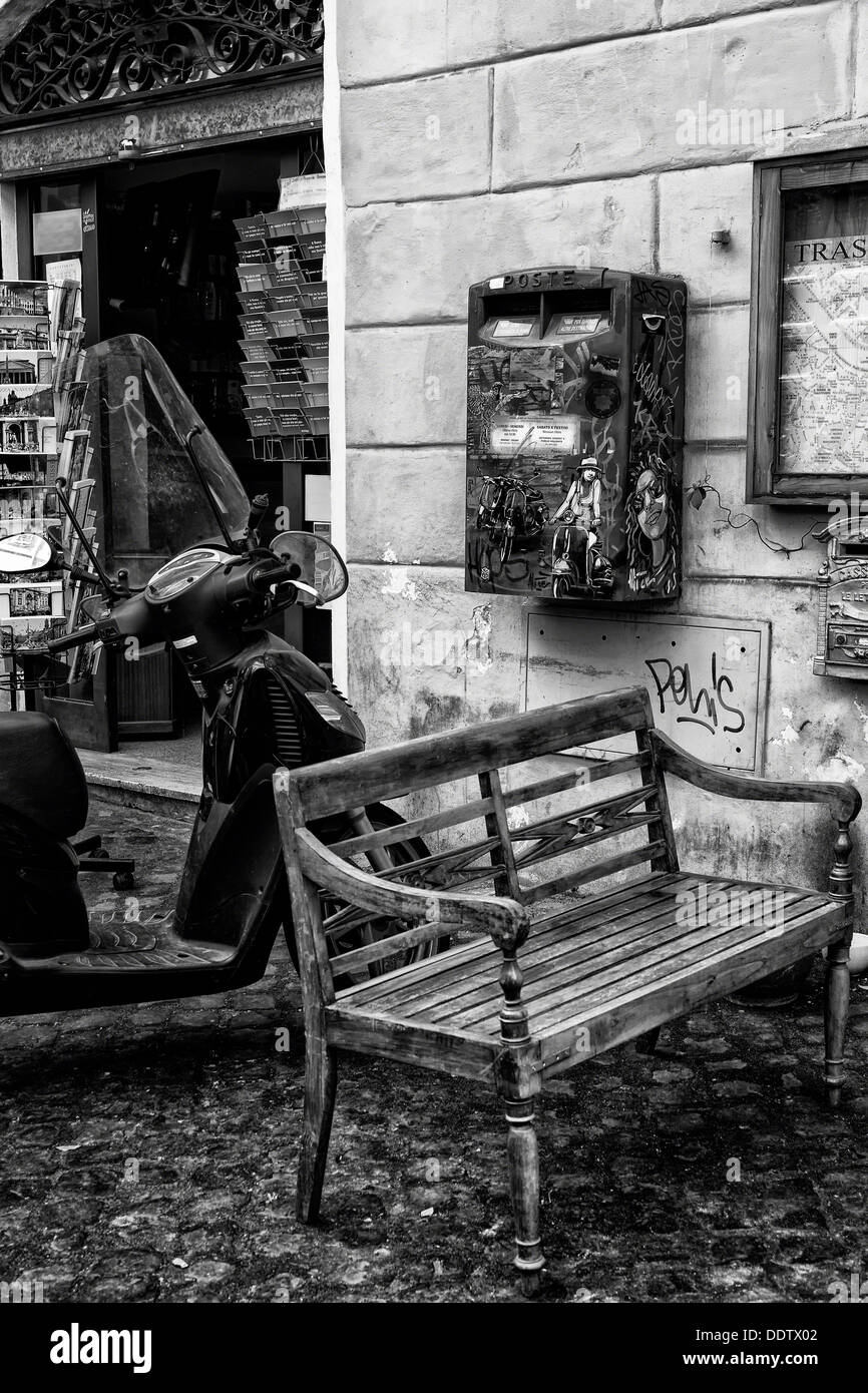 Trastevere street: wooden bench, parked motorbike, and graffiti-covered red letterbox outside shop selling postcards, close up m - Stock Image