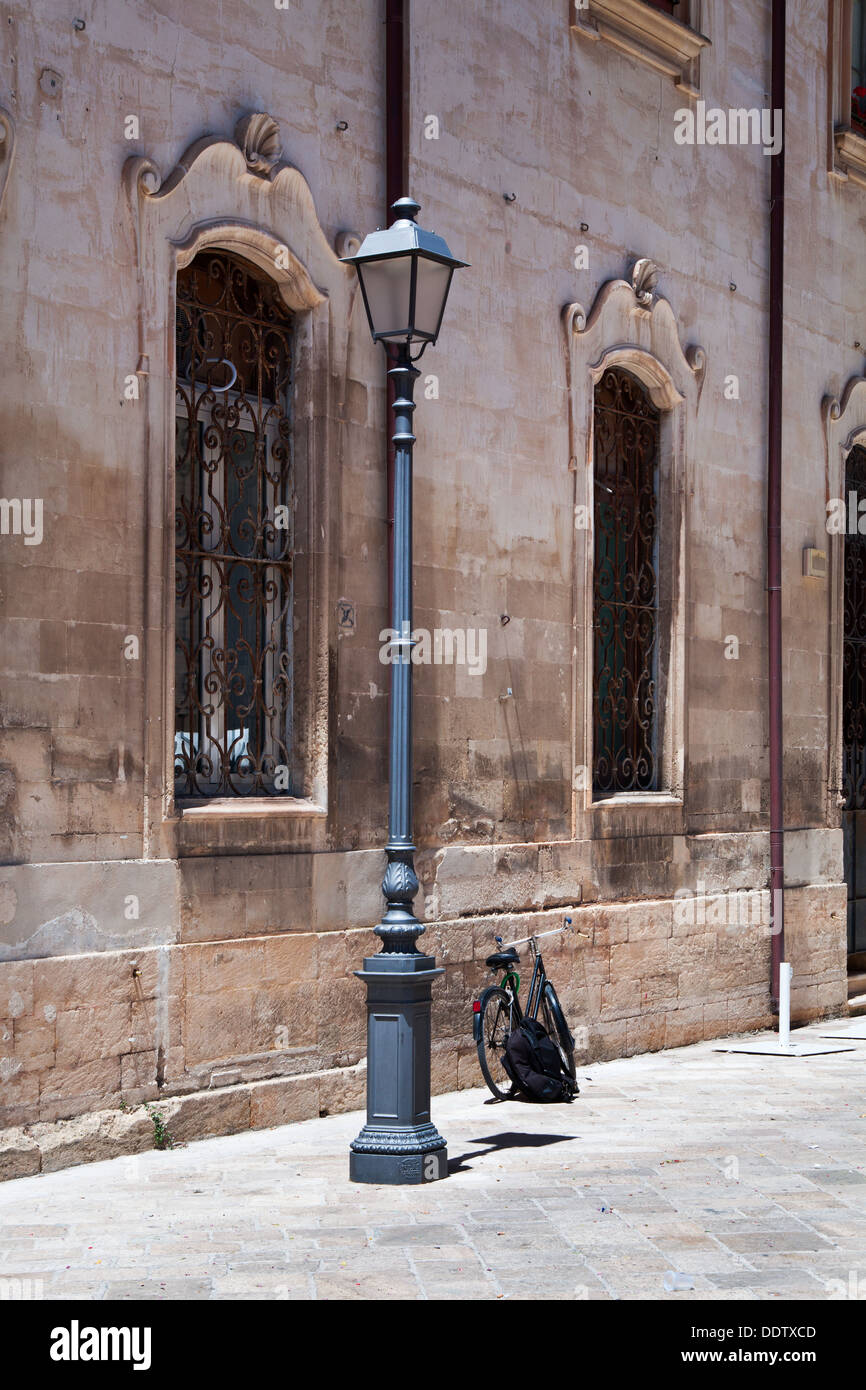 Sreet view detail with facade of  Renaissance palazzo, wrought iron grille over 2 windows, metal lamp post, and parked bicycle a - Stock Image