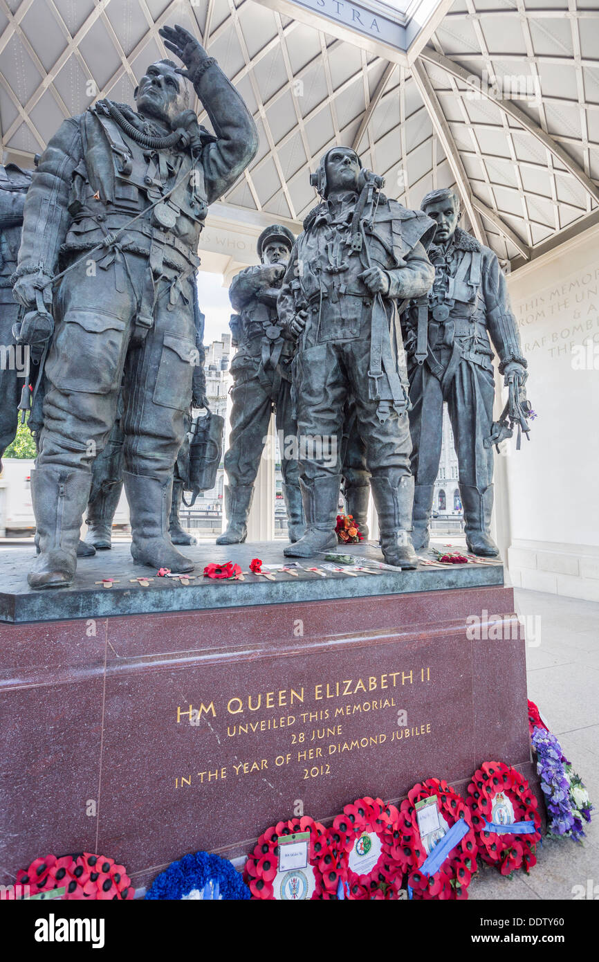 RAF Bomber Command Memorial, Green Park, London, England with statues of heroic airmen of WWII and red and blue poppy wreaths laid around base - Stock Image