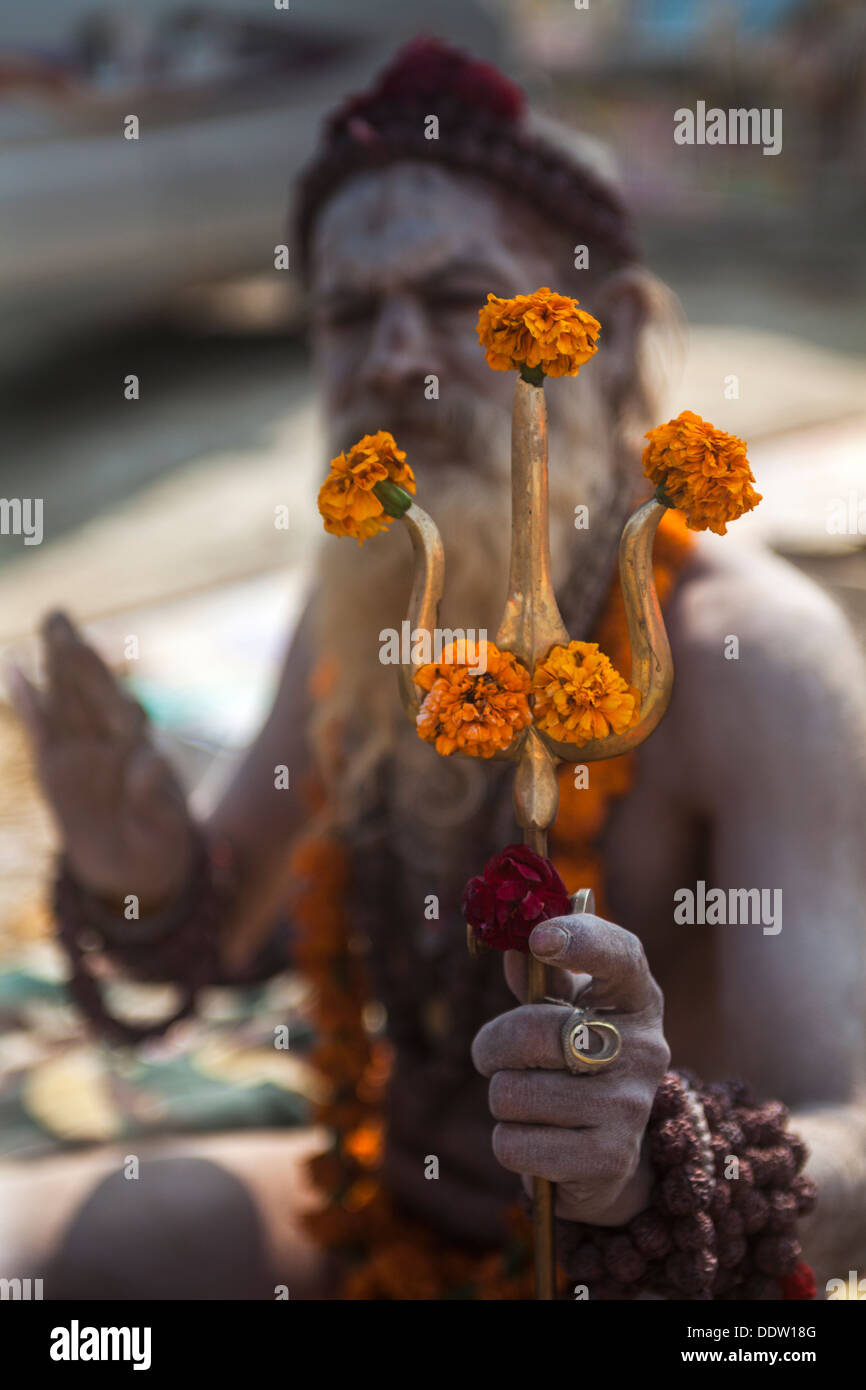 Naga Sadhu and his ornament the great trident decorated with Marigold flower at Kumbh Mela 2013, India - Stock Image