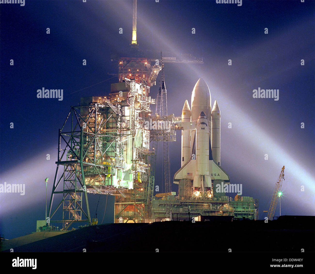 A timed exposure of the first Space Shuttle mission, STS-1, at Launch Pad A, Complex 39, turns the space vehicle and support facilities into a night-time fantasy of light. To the left of the Shuttle are the fixed and the rotating service structures. - Stock Image
