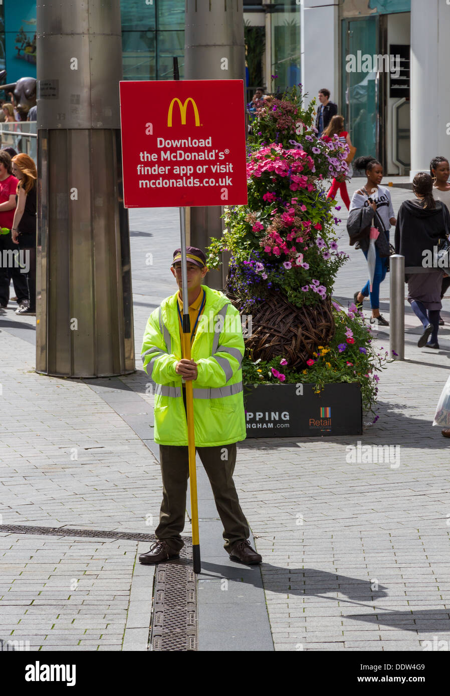 McDonalds worker in Birmingham holding a placard to advertise the McDonalds smartphone app. - Stock Image