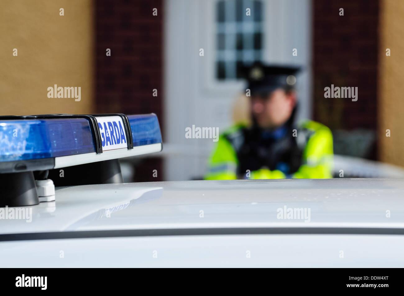Garda Siochana Irish police officer behind a car Stock Photo