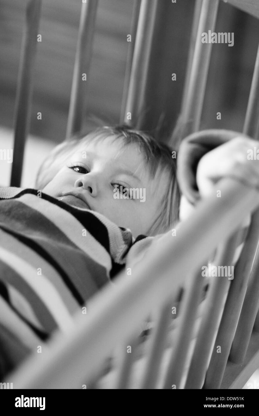 Black and white image of an unhappy toddler lying down and holding onto his cot bars. - Stock Image