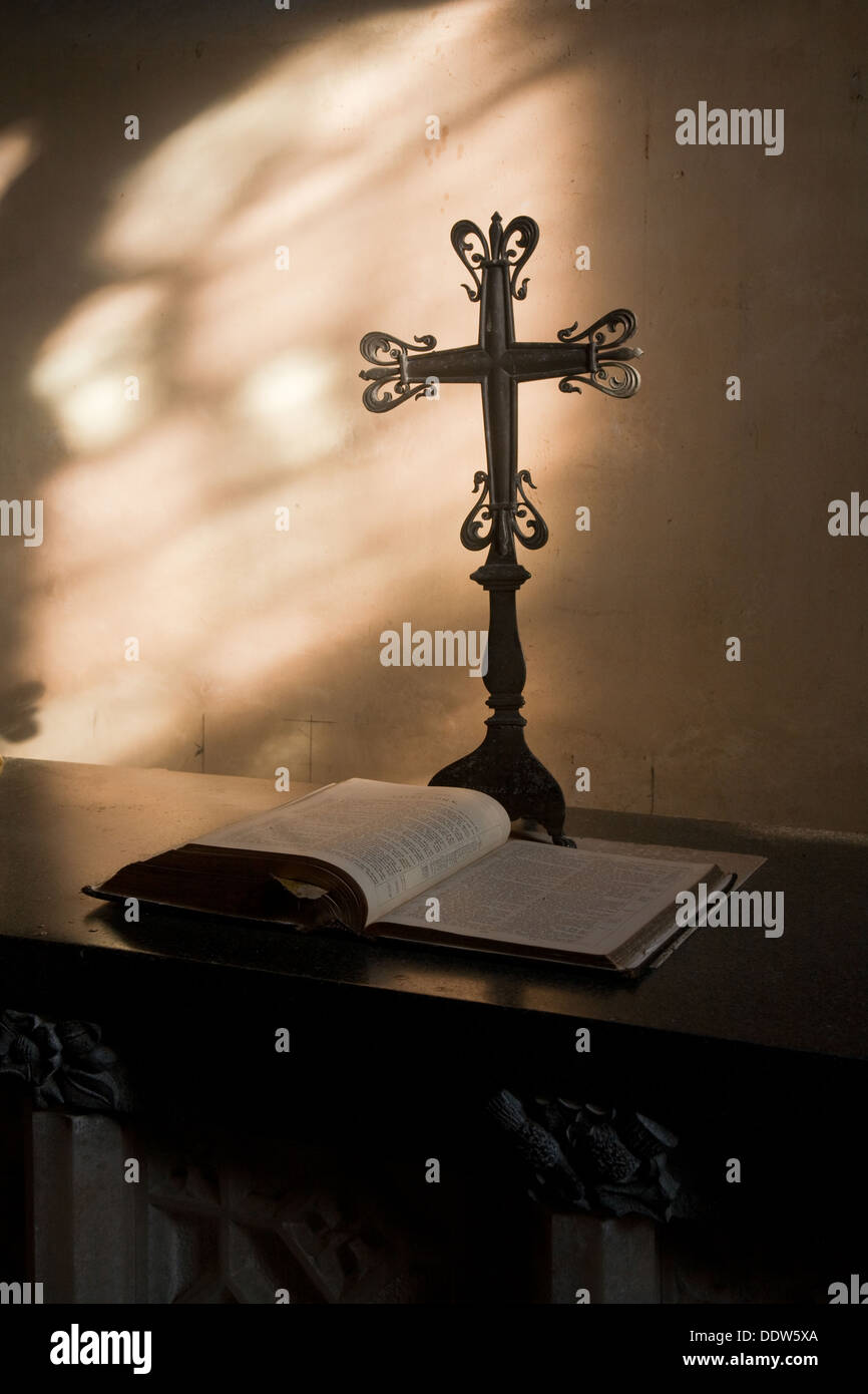 Detail from the interior of a church with a decorative cross on a stand and Bible on table, lit from side glass window. - Stock Image