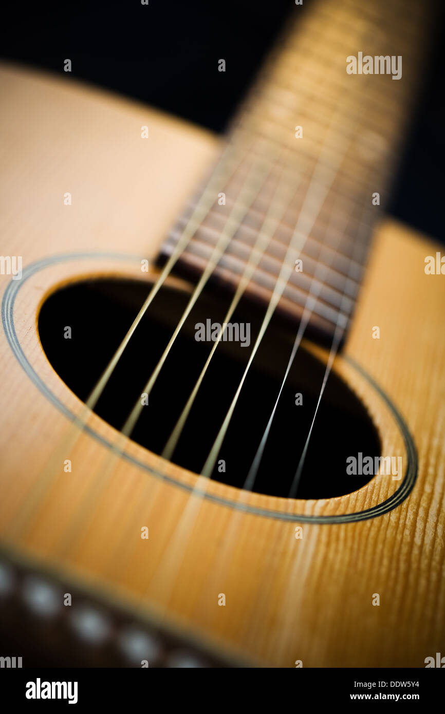 Acoustic guitar. Close-up on sound hole and neck. Very shallow depth of field and vignette. - Stock Image