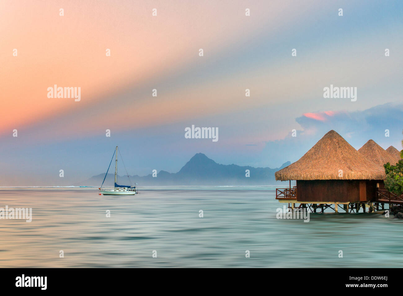 bungalows over water with sailboat and sunrise and Moorea , Tahiti - Stock Image