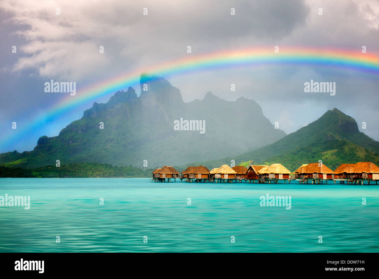 Bungalows over water with rainbow and Mt. Otemanu. Bora Bora. French Polynesia Stock Photo