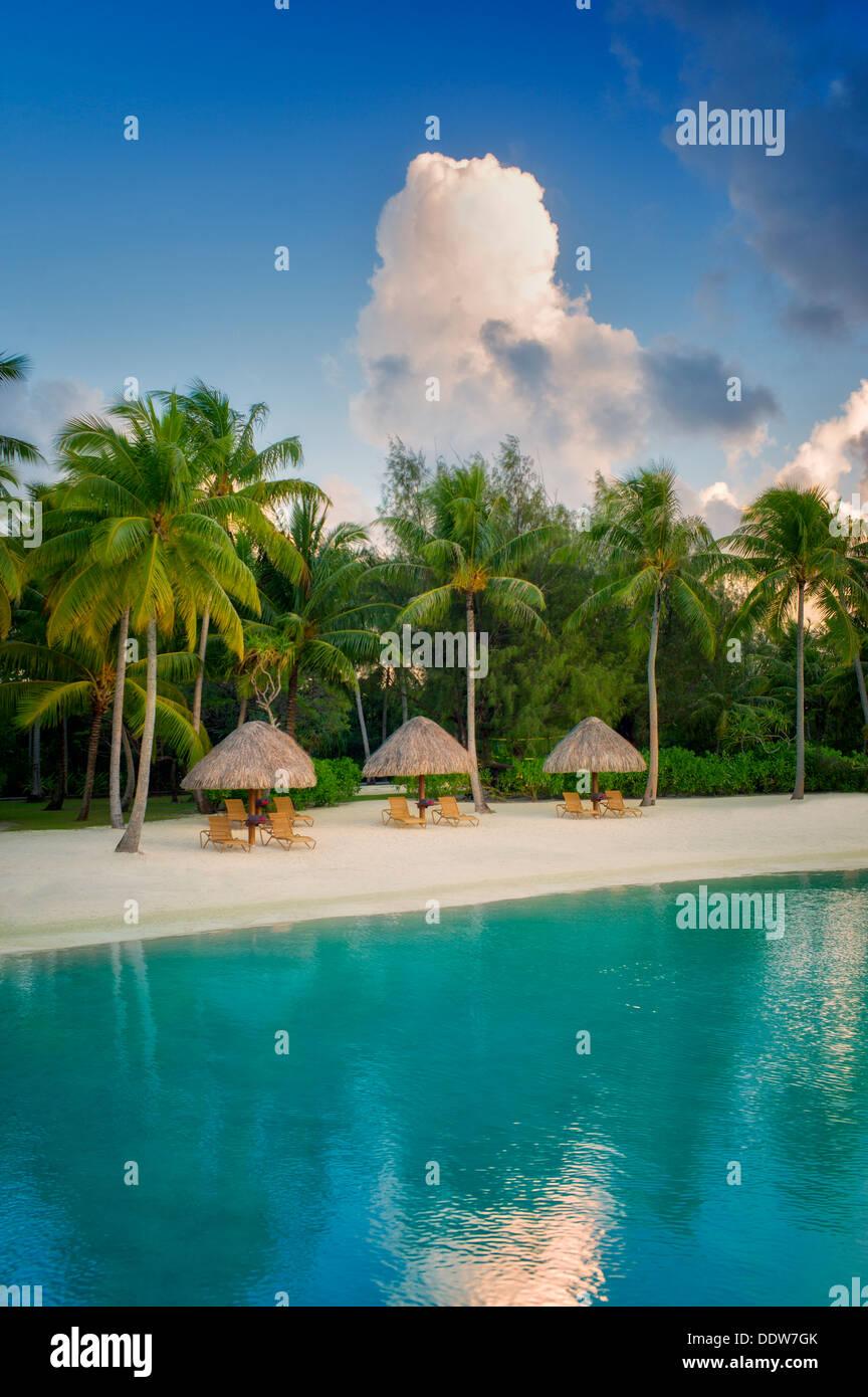 Umbrellas and chairs on lagoon beach. Bora Bora. French Polynesia. - Stock Image