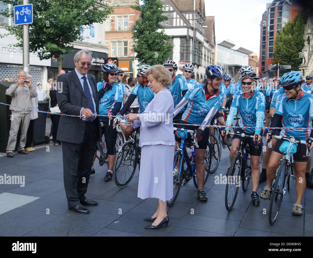 Mr. Michael Turnbull, chairman of Hope, holds the tape for Lady Gretton, Lord Lieutenant of Leicestershire. who is about to cut it and send the riders off on their 410 mile journey. - Stock Image