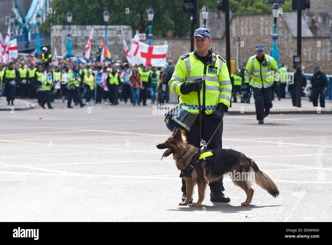 London, UK. 7th September 2013. a police officer with a dog stands ahead of hundreds of EDL supporters that attend the protest against what they see as the influence of Islam in the Tower Hamlets area. Credit:  Piero Cruciatti/Alamy Live News - Stock Image