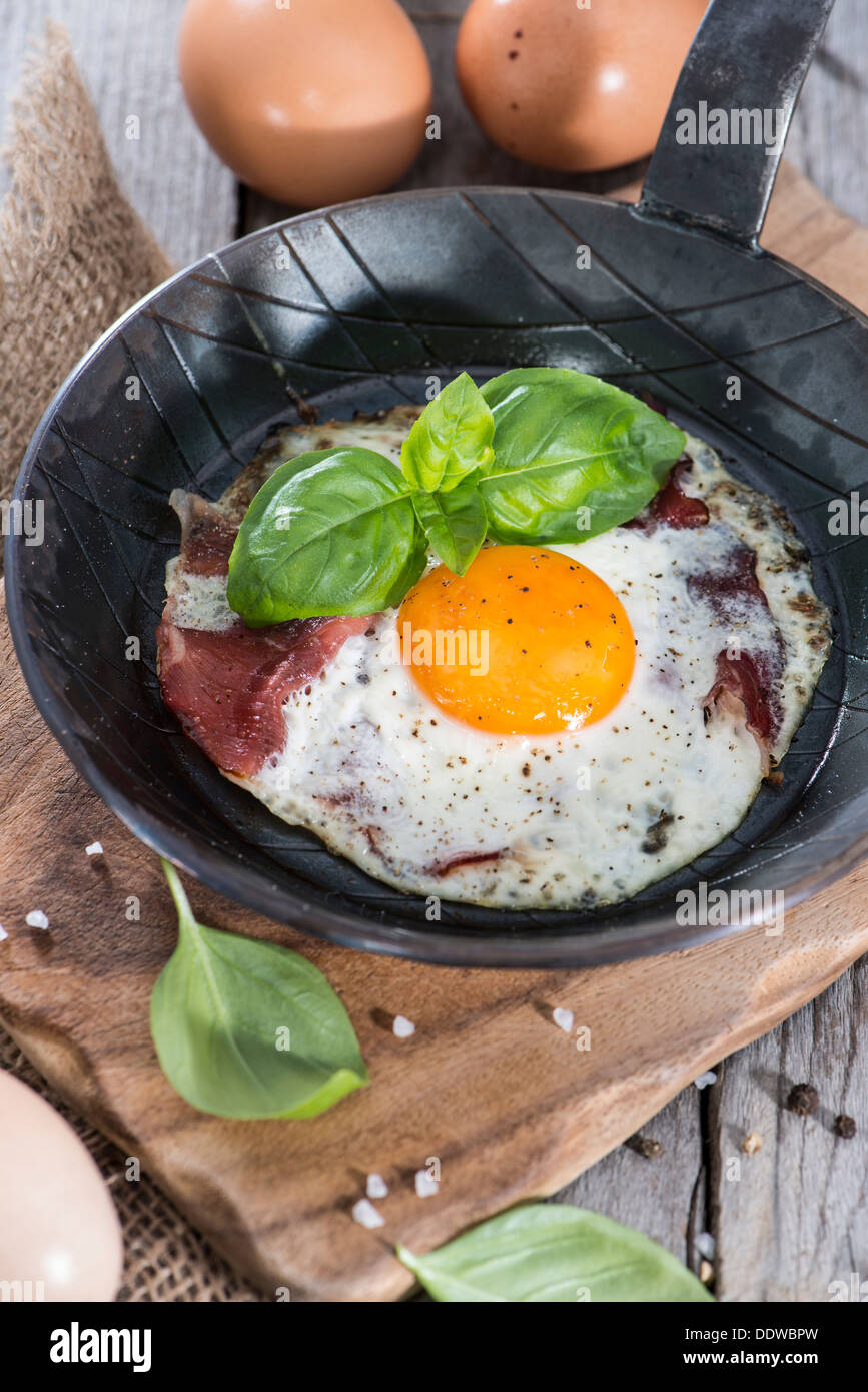 Fried Egg in a small Pan on vintage wooden background - Stock Image