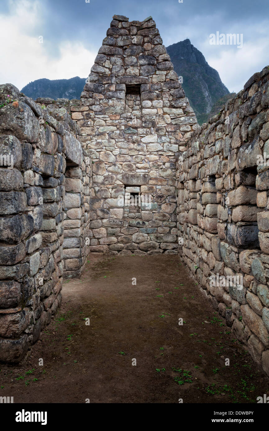 Machu Picchu Inca ruins : urban sector building  with typical niches and trapezoidal windows, Machu Picchu mountain beyond, stor - Stock Image