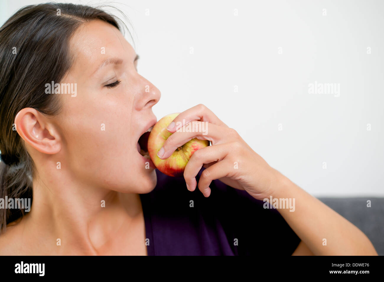 woman is frustratedSide view of an attractive young woman biting into a fresh juicy red apple as she follows a healthy diet and - Stock Image