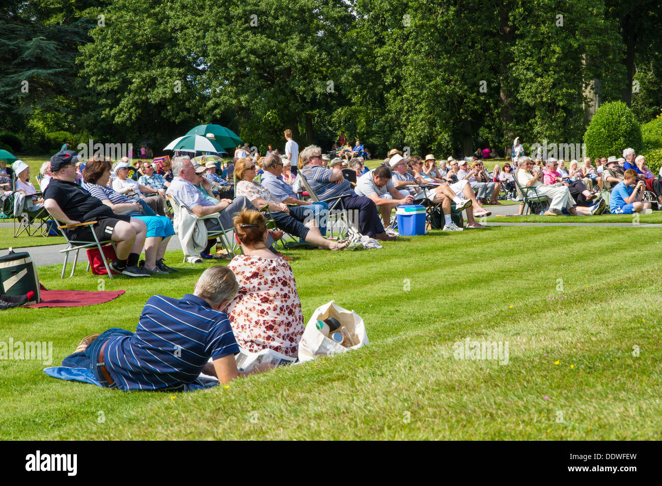 Visitors to Brodsworth Hall in Doncaster sat on the lawn in the sunshine listening to the afternoon band concert. - Stock Image