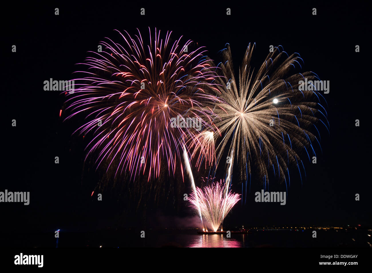 fire works fire crackers at night over the water - Stock Image