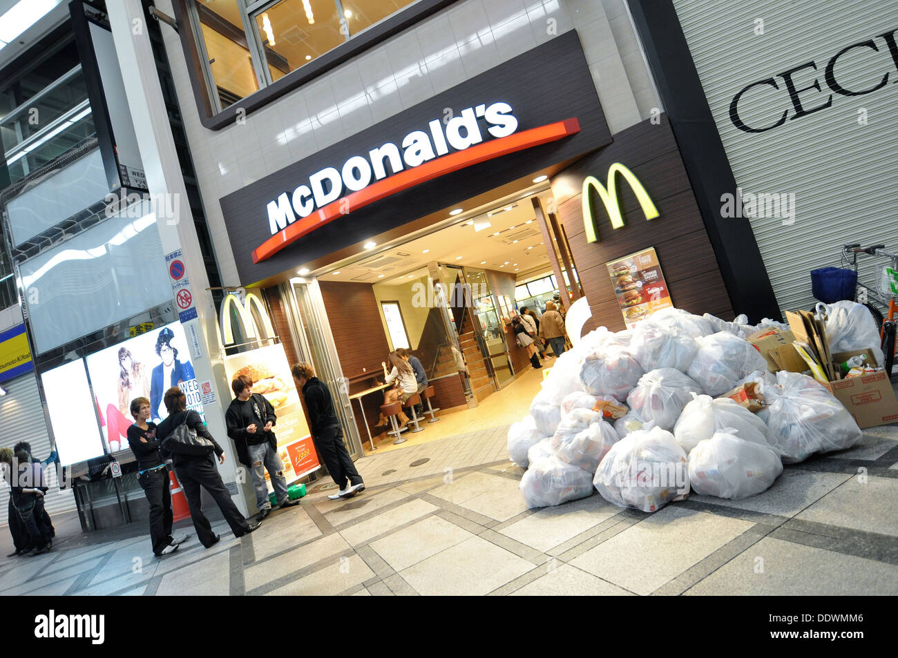 A McDonald's fast food restaurant with a lot of garbage piled up outside. - Stock Image