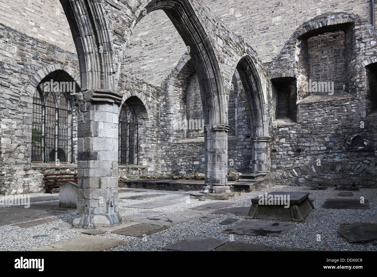 Detail of cloister of St. Auden's church, monochrome, showing Romanesque columns and arches, with tombstones set into ground, Du - Stock Image