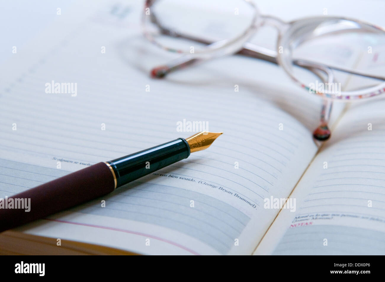 Fountain pen and eyeglasses on a diary. Close view. - Stock Image