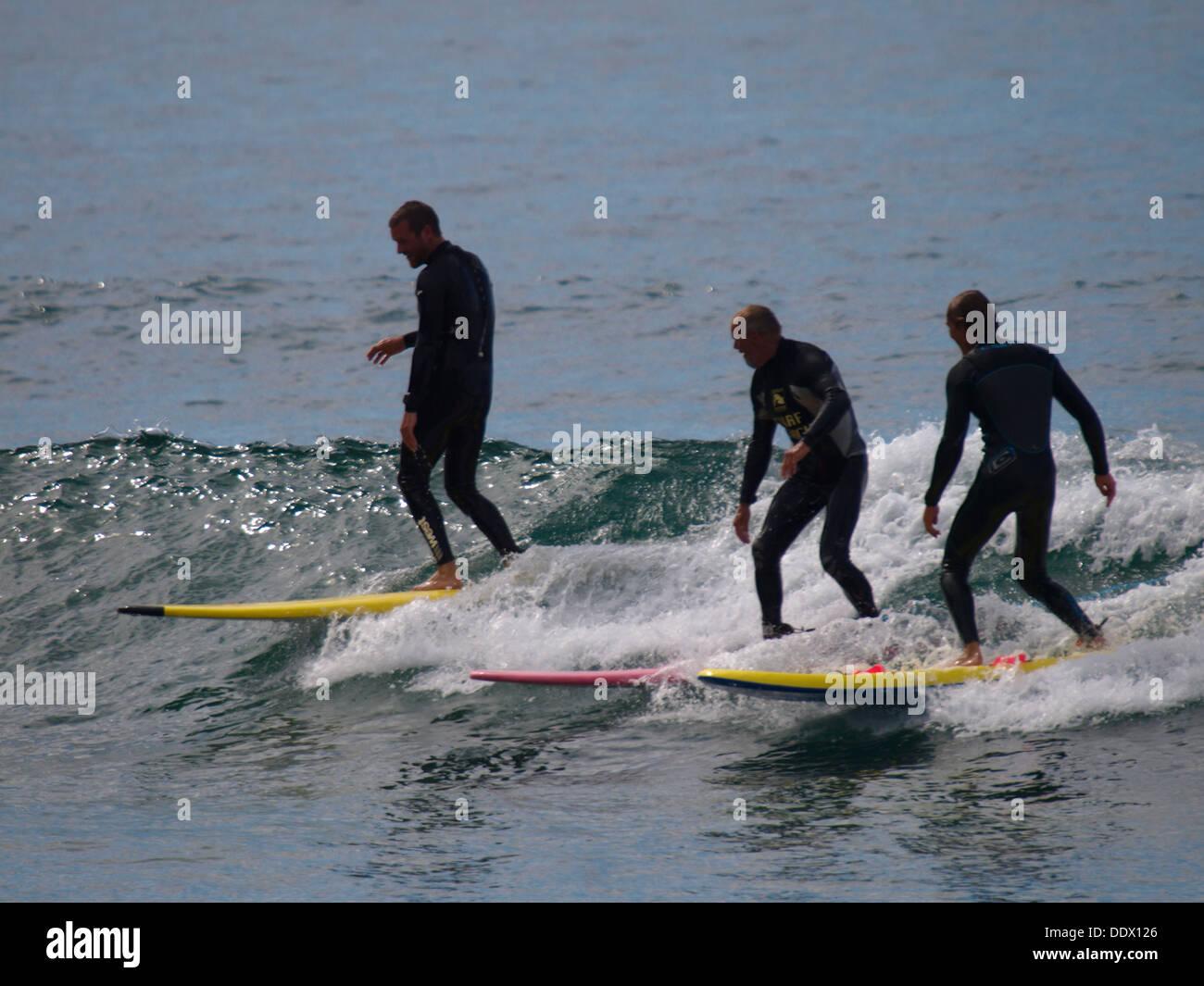 Three surfers on the same wave, Trebarwith Strand, Cornwall, UK 2013 - Stock Image