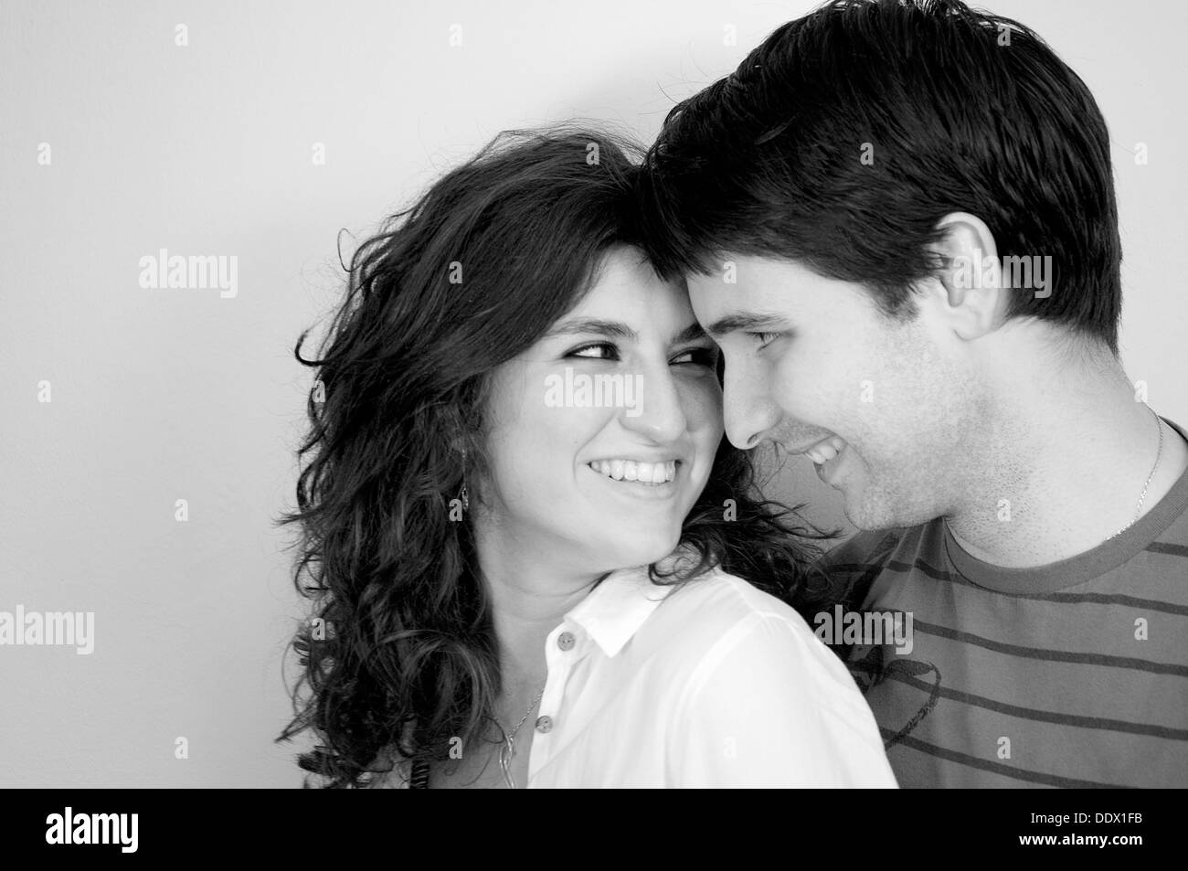 Happy young couple smiling and looking at each other. Close view. Black and white. - Stock Image