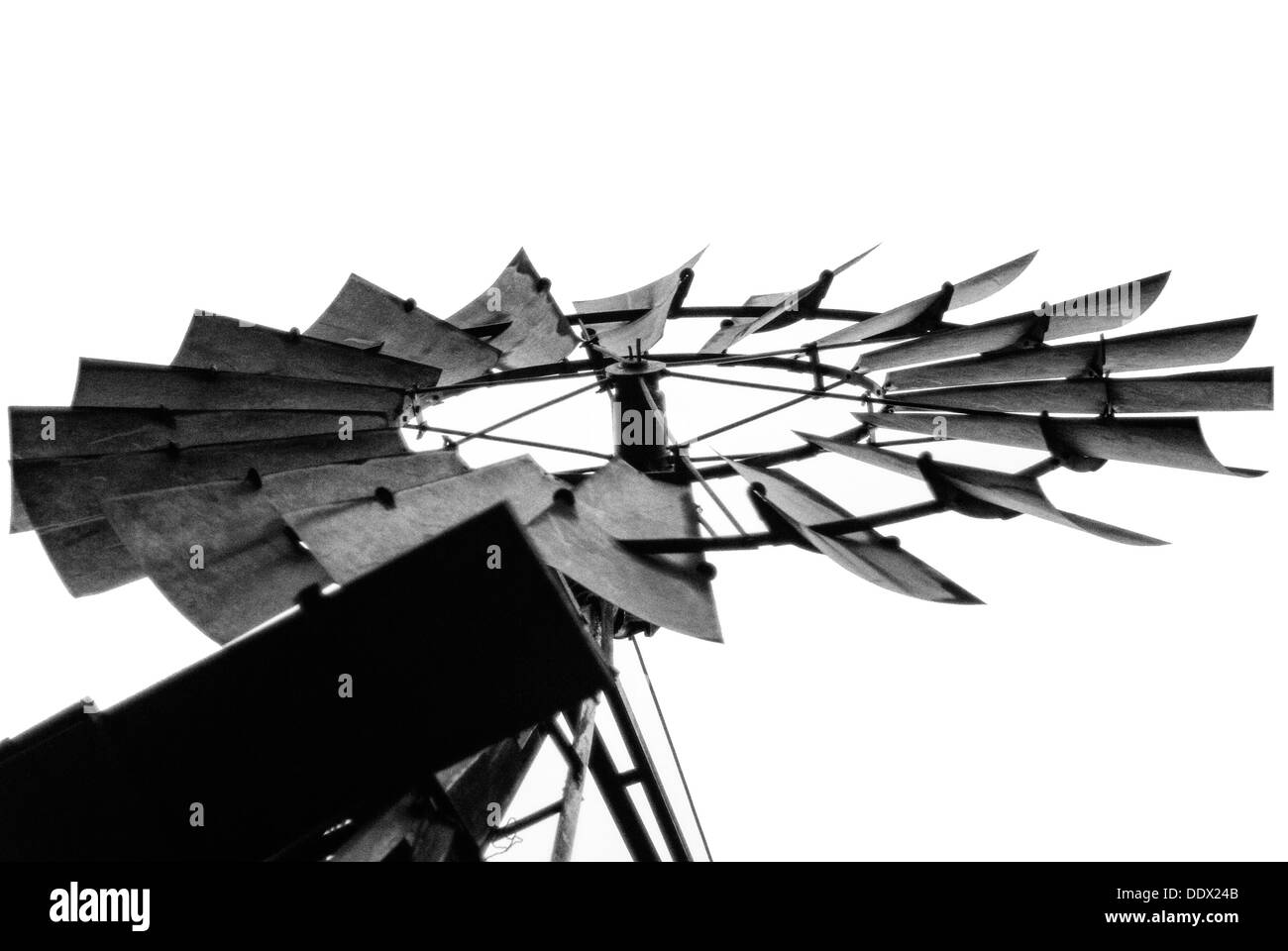 A black and white photo of a water pumping windmill taken from below - Stock Image