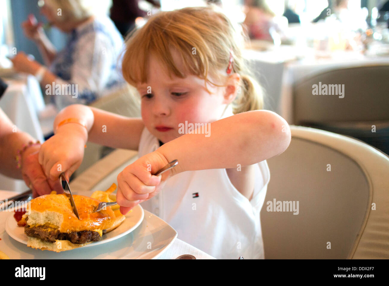 Four year old girl cutting into a cheeseburger - Stock Image