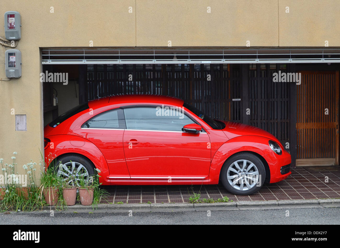 A bright red VW Beetle. - Stock Image