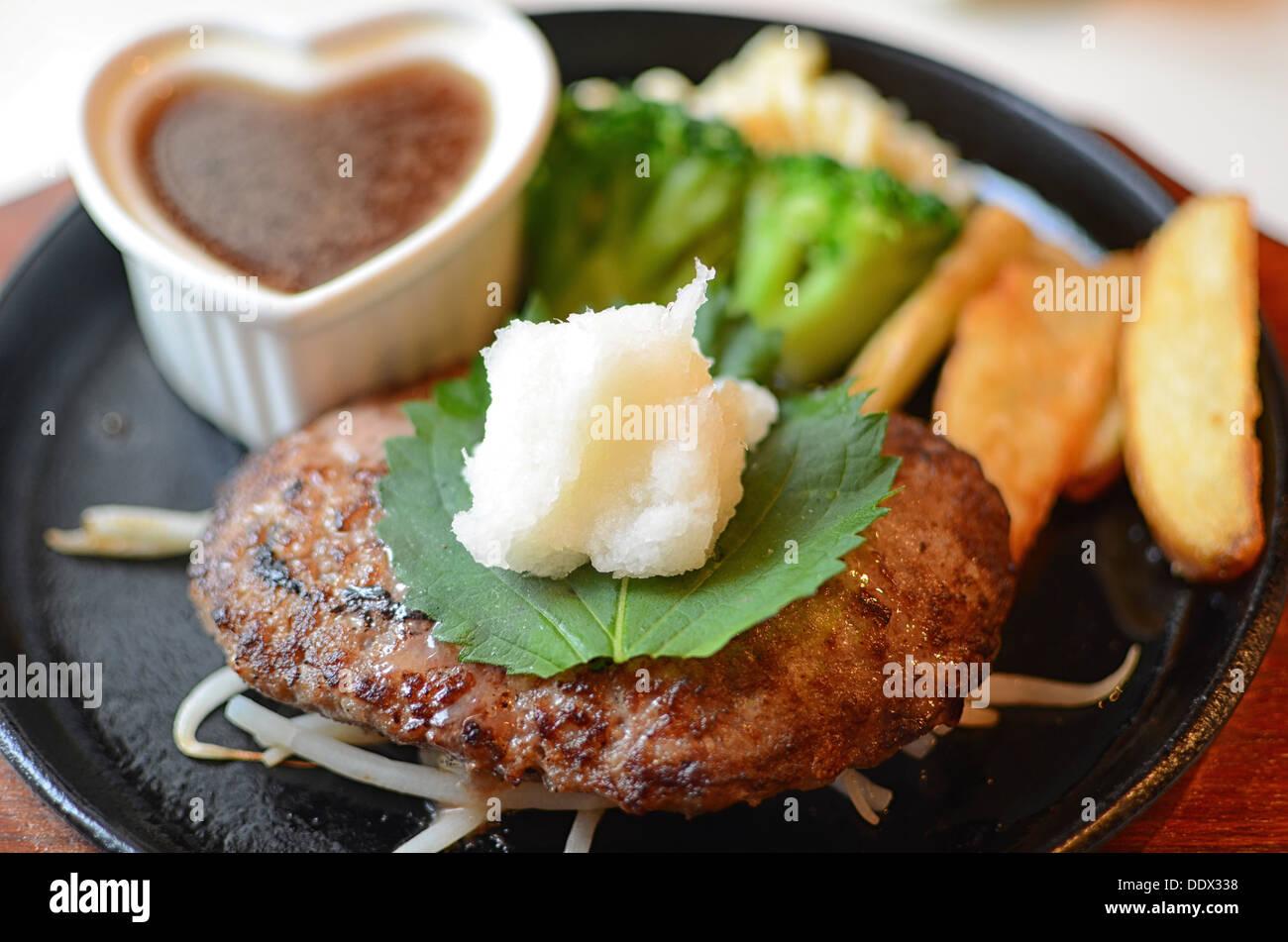 A hamburger Japanese style (hamburg). On top is grated Japanese radish. - Stock Image