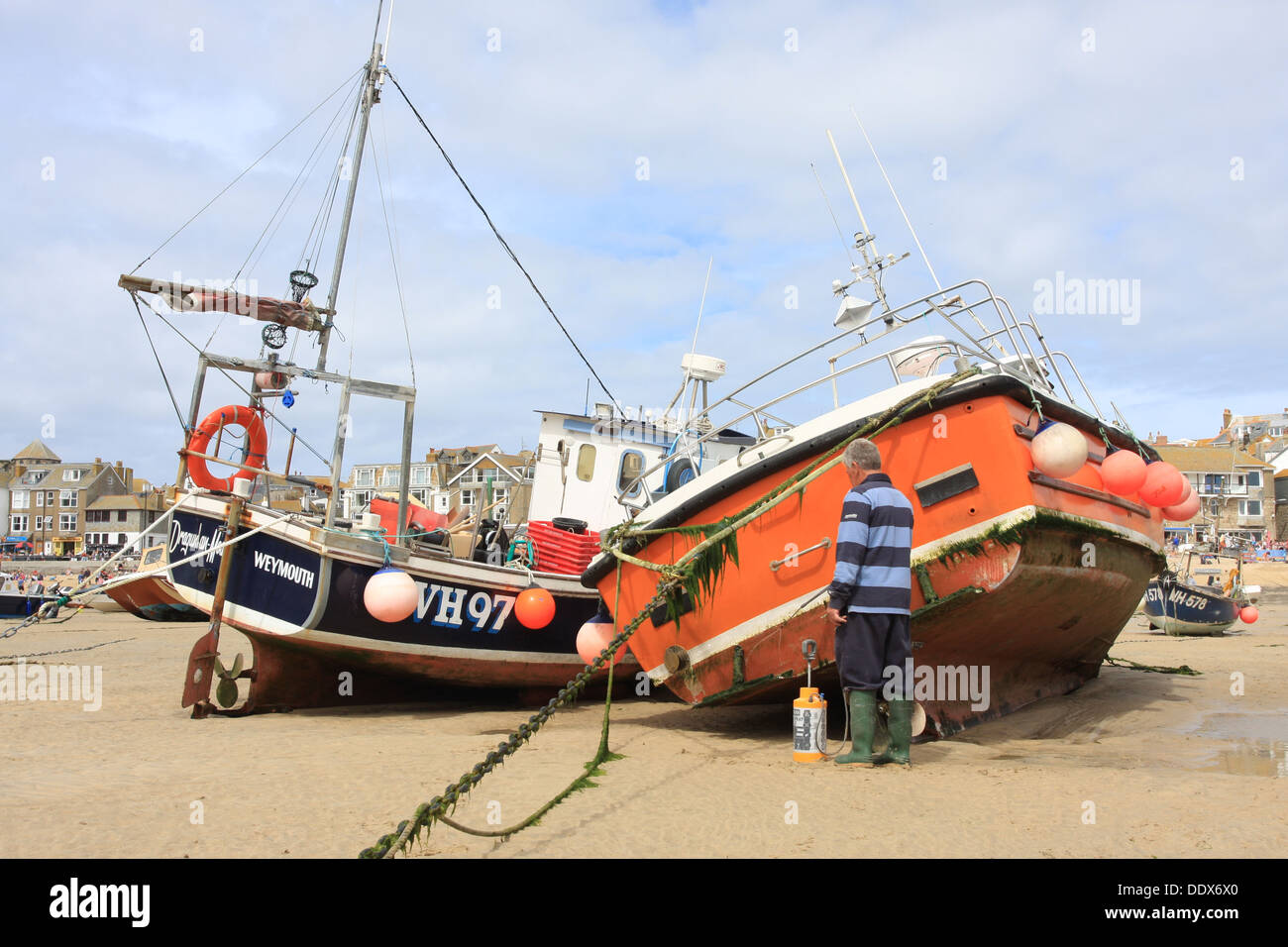 A man cleans algae from the hull of a fishing boat in St,Ives harbor. - Stock Image