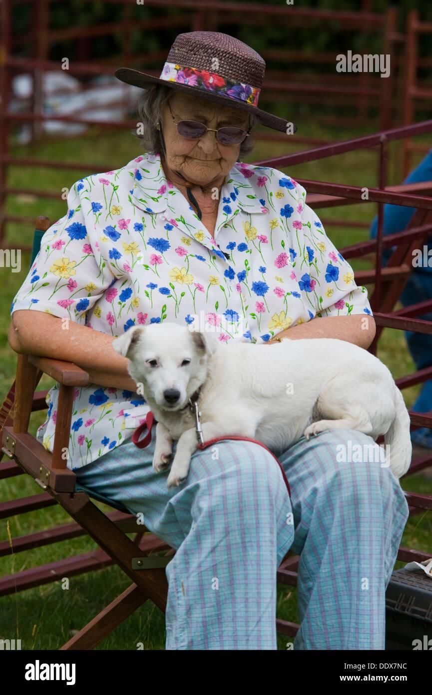 Elderly lady asleep sitting with dog on her lap at Cwmdu Village Show Powys Wales UK - Stock Image
