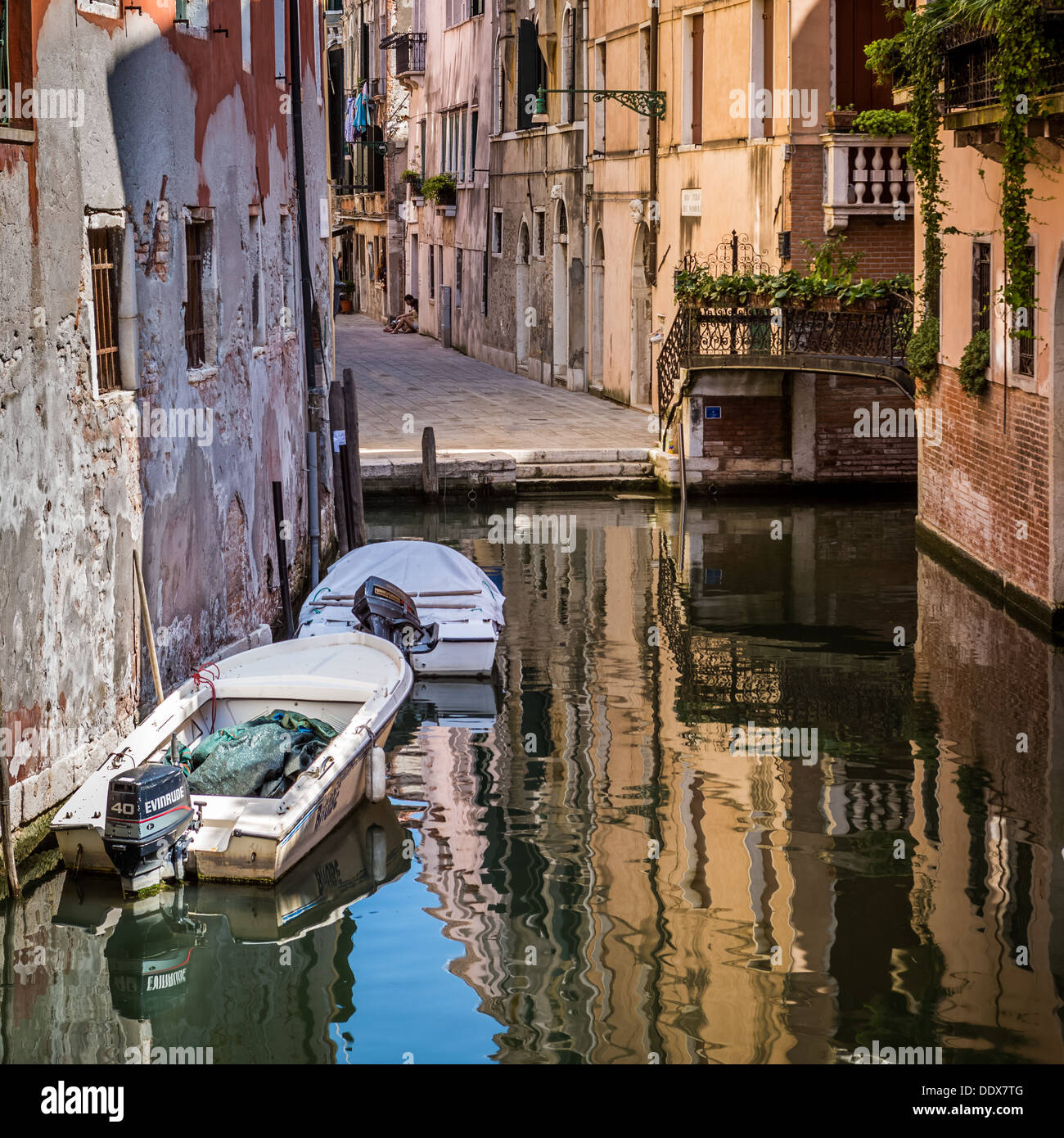 Typical venetian canal with the historic buildings reflected in the water - Stock Image