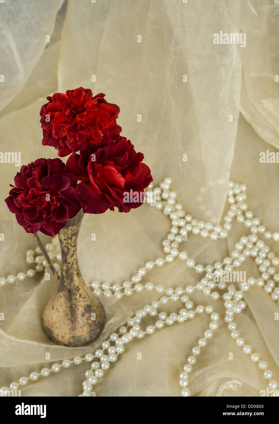red roses in an antique silver vase with pearls on cream colored ...
