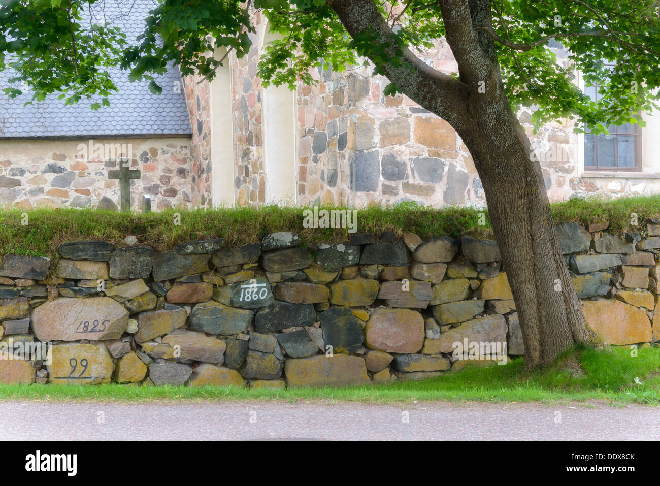 Dry stone wall and tree with church, Torsång, Dalarna, Sweden - Stock Image