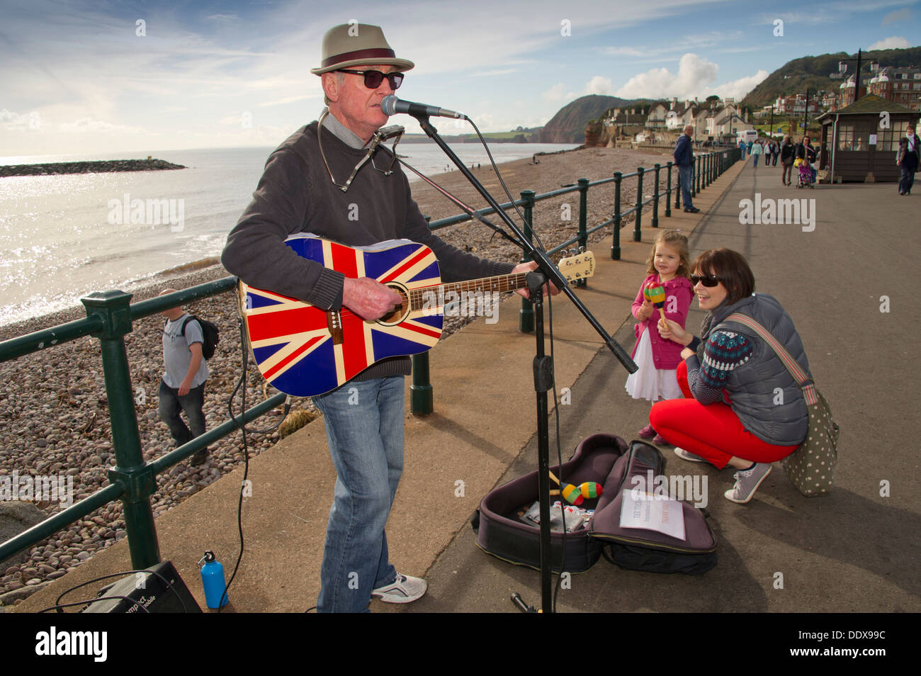 Sidmouth,Devonshire,UK,a seaside town on the South Coast with a promenade and beach,busker and beached boats.a UK sea coast - Stock Image