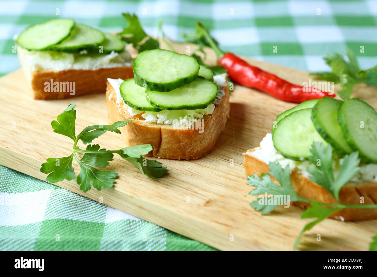 canape with cheese and fresh cucumber, food close up - Stock Image