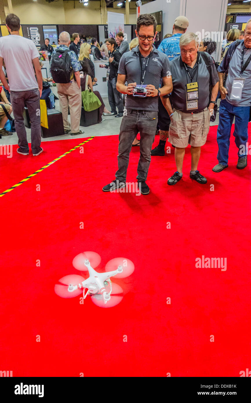 A young adult demonstrates the DJI Quadcopter as he stoops down on the red carpet at Photoshop World 2013 in Las Vegas. - Stock Image