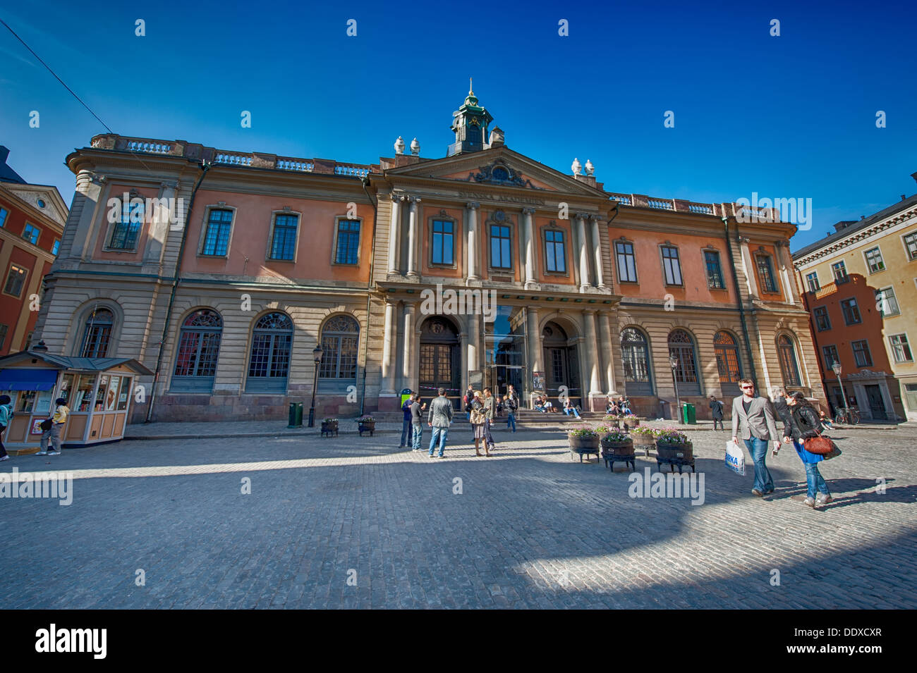 Tourists admire the Stockholm stock exchange building. The building in the Old Town is the home of the Swedish academy. - Stock Image