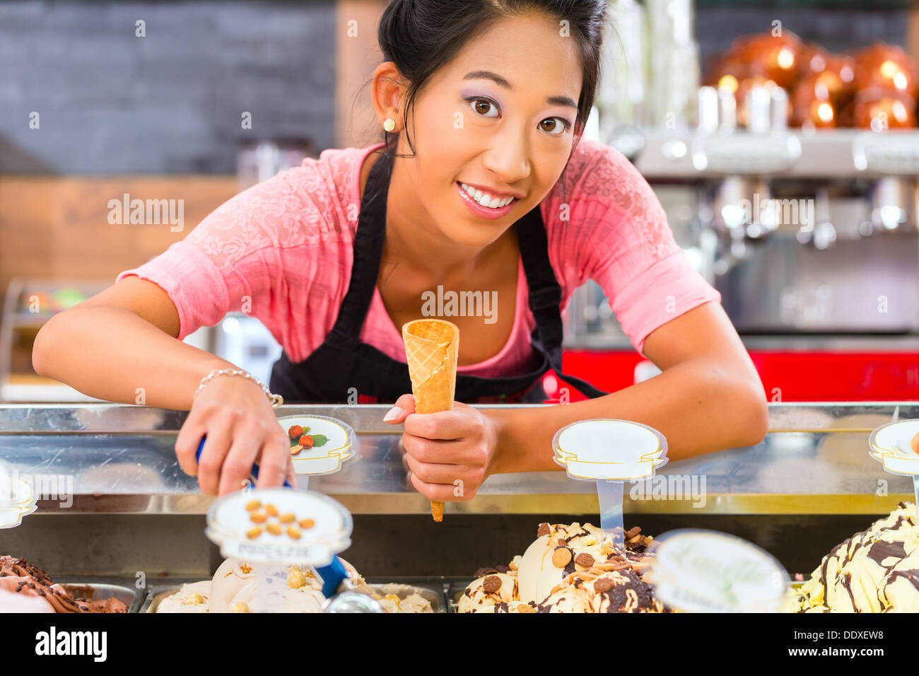 Young Asian saleswoman in an ice cream parlor takes a scoop of ice cream Stock Photo