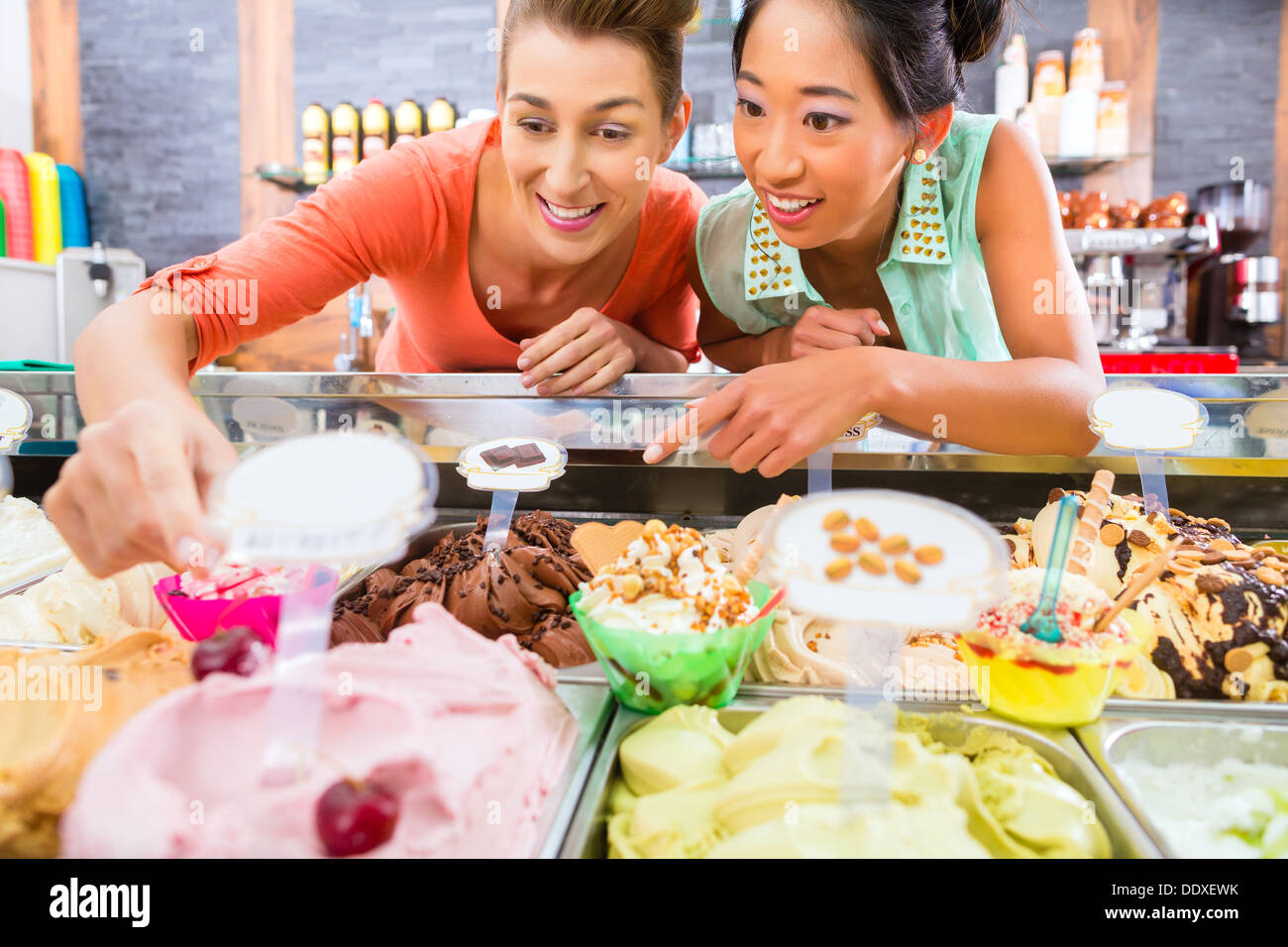 Young female customers or friends with sorts of ice cream for cornets and cones and sundaes in parlor Stock Photo