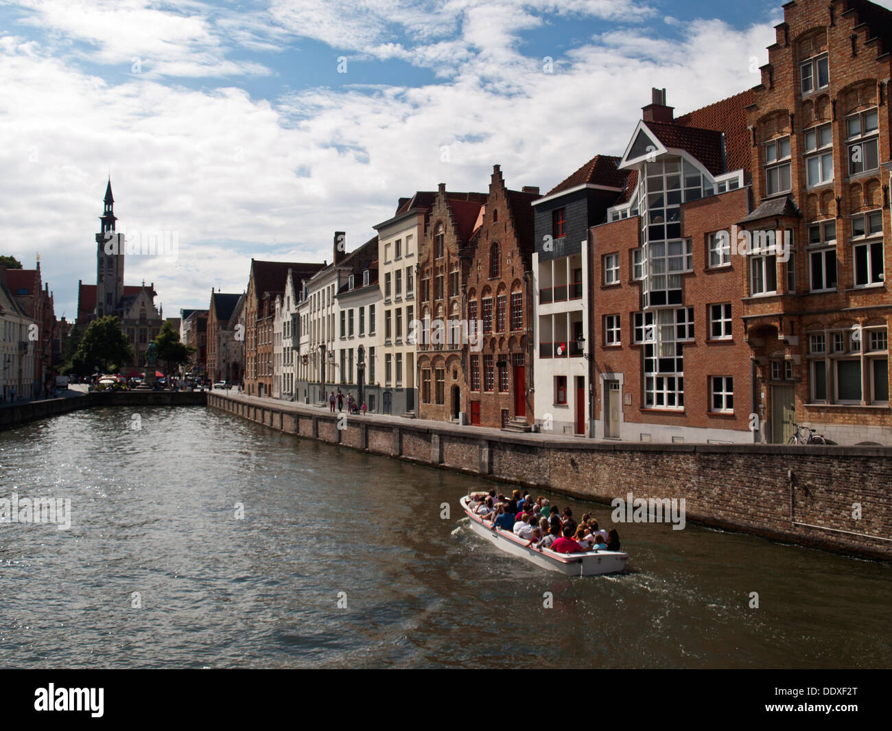 Bruges guilded canal houses and tourist boat - Stock Image