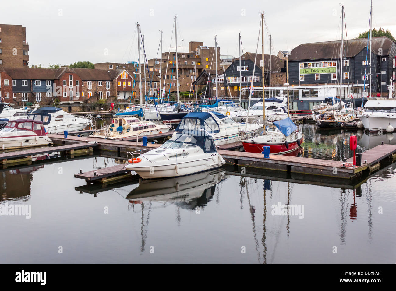 St Katharines Docks Yacht Marina with Sail and Motor Boats and the Dickens Inn - Stock Image