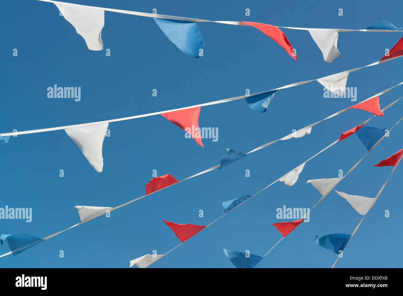 Strips of red, white and blue bunting line diagonally across a clear cloudless sky in Poole, Dorset. - Stock Image