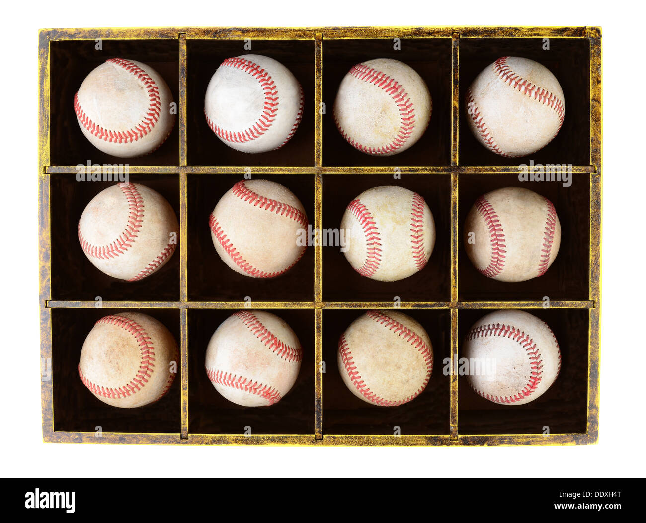 A dozen scuffed baseballs in a divided wooden box. Horizontal format over white. - Stock Image