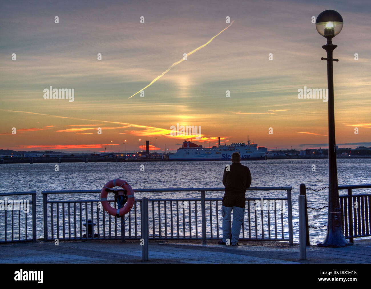 Man looking over to Birkenhead-Belfast Stena line ferry, from Albert Dock at Nighttime liverpool Merseyside England UK - Stock Image