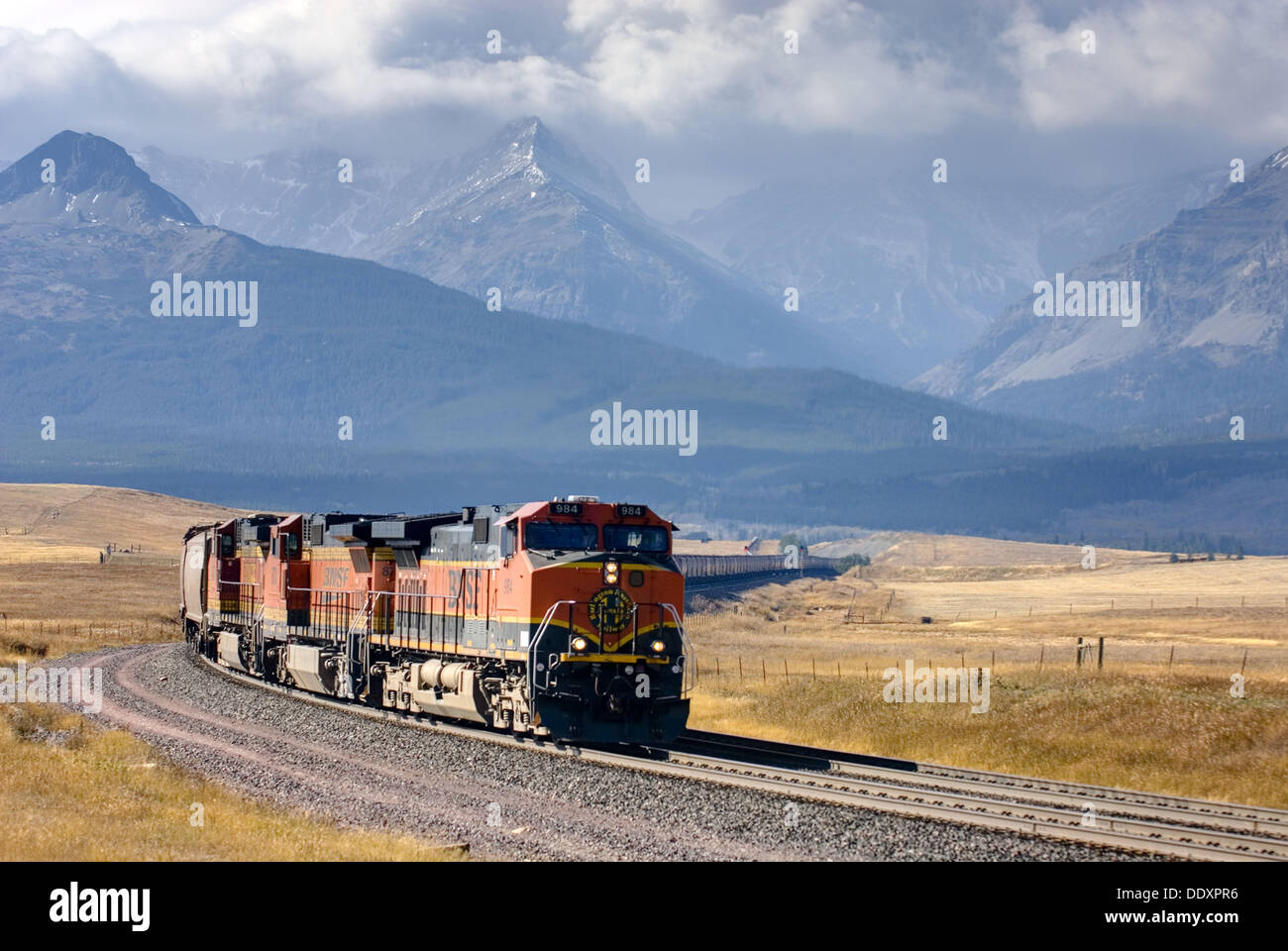 Freight train on the Montana plains near the Rocky Mountain Front Ranges of Glacier National Park USA - Stock Image