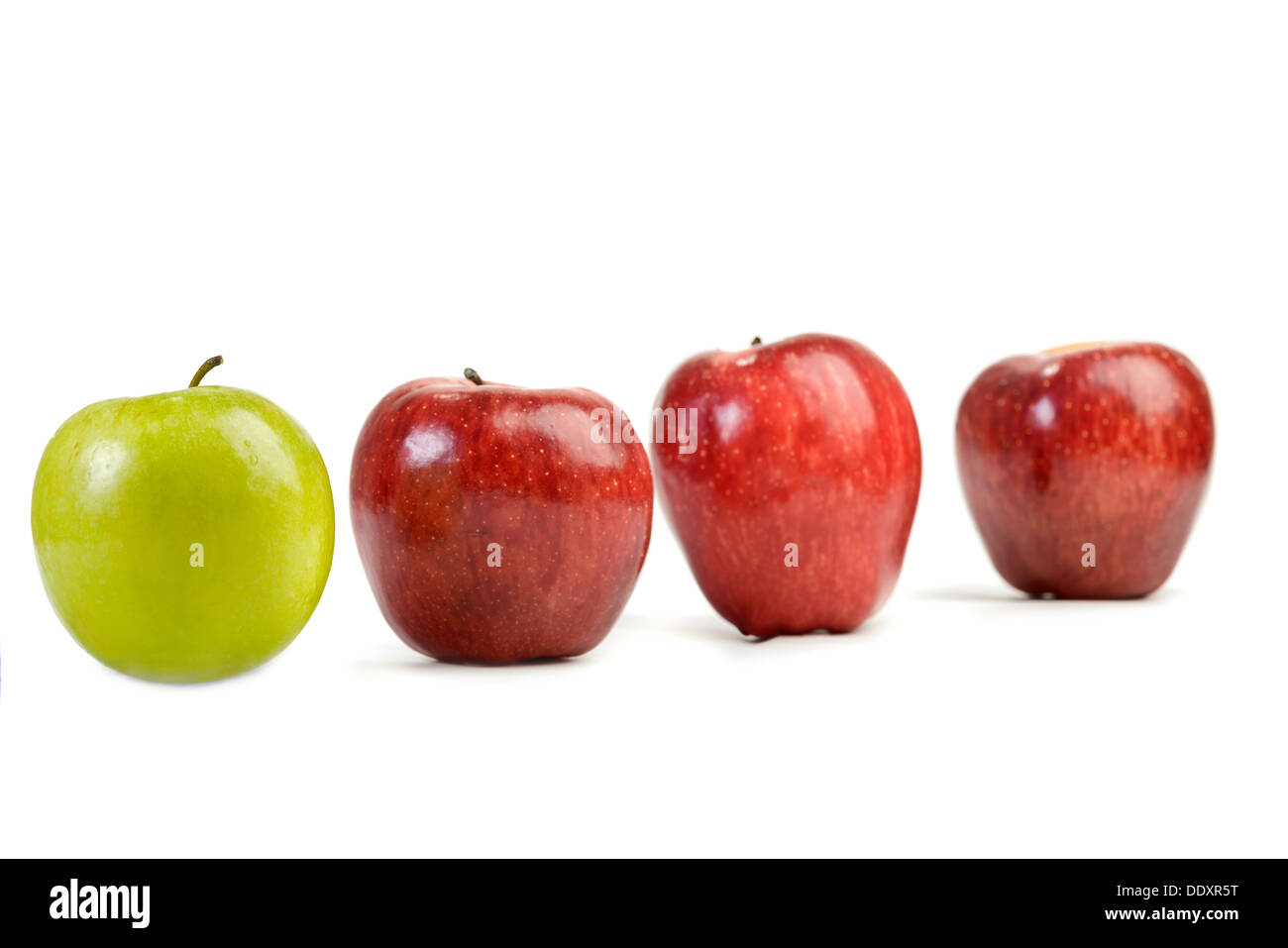 Ripe red apples and one green apple isolated on white - Stock Image