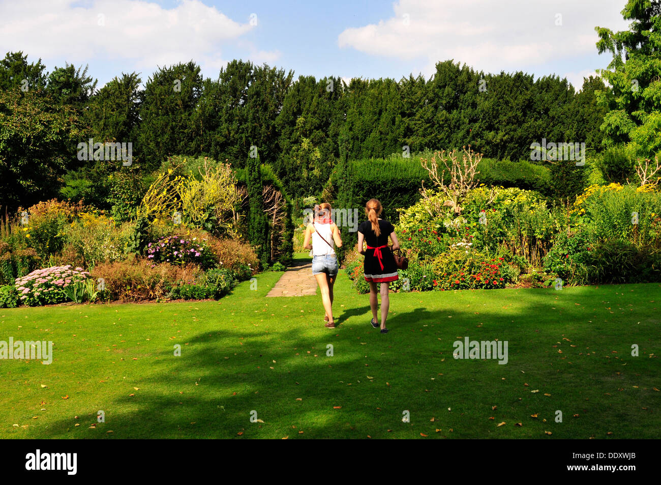 Two young women walking in Fellows Garden, Clare College, Cambridge, UK - Stock Image