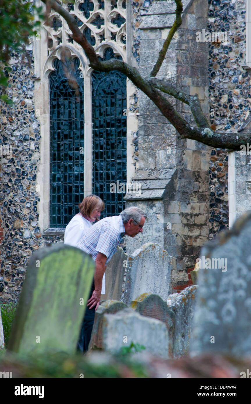 Couple looking at grave stones in church yard genealogy - Stock Image